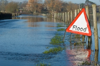 Flooded road with triangular flood warning temporary road sign